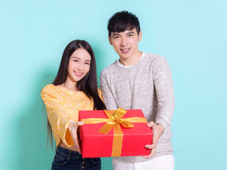 Happy young couple showing gift.Isolated on blue background.