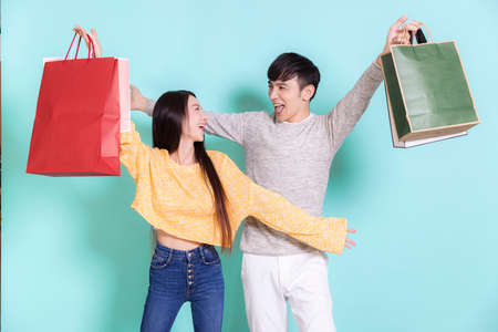 Excited young couple holding shopping bags. Looking at each other.Isolated on blue background. Фото со стока