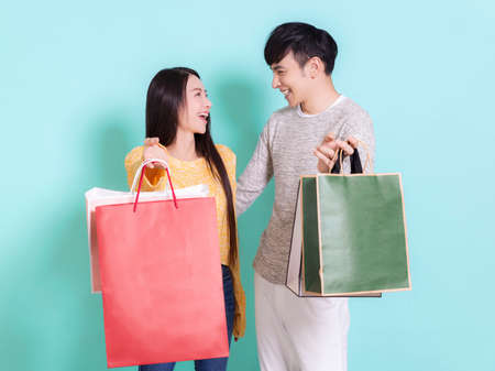 Happy couple with shopping bags.Looking at each other.Isolated on blue background. Фото со стока