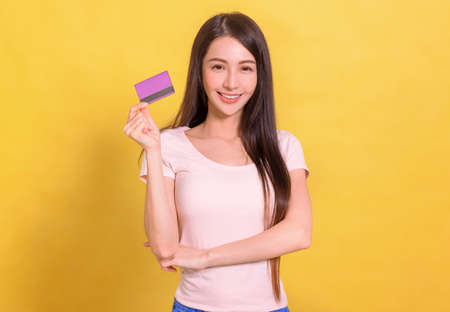 beautiful Asian woman showing credit card for making payment or paying online