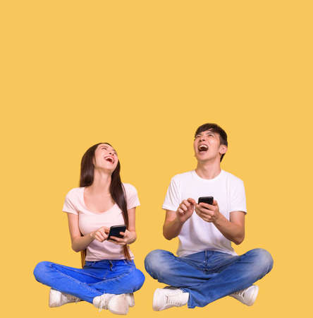 Excited young couple using mobile phone and looking above