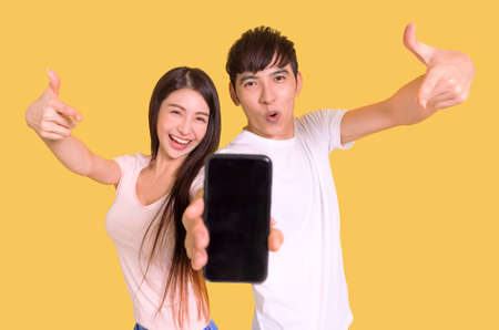 Happy Young couple pointing and showing the blank smartphone screen