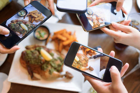 Group of friend taking picture with smart phone before dinner. top view. Фото со стока