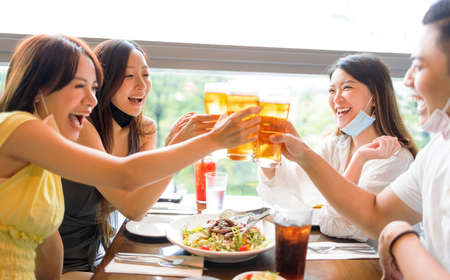 Happy Friends drinking beer in  restaurant  with face mask on to be protected Фото со стока