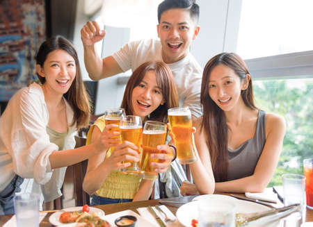 Young friends enjoying food and drink in restaurant
