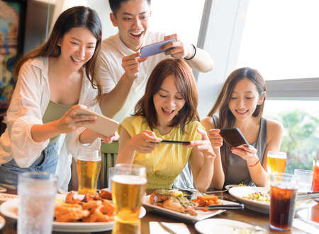 Happy young group taking  picture with smart phone before dinner