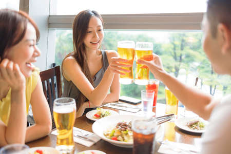 Happy Young friends enjoying food and beer in restaurant