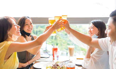 Happy people drinking beer in  restaurant  with face mask on to be protected Фото со стока