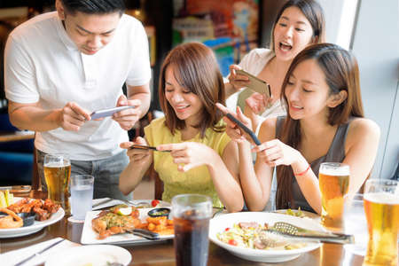 Happy young people taking  picture with smart phone in restaurant