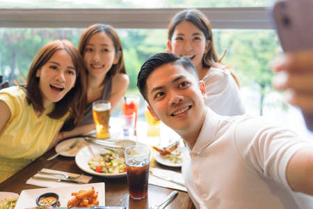 Happy young  people sitting in  restaurant and taking  selfie
