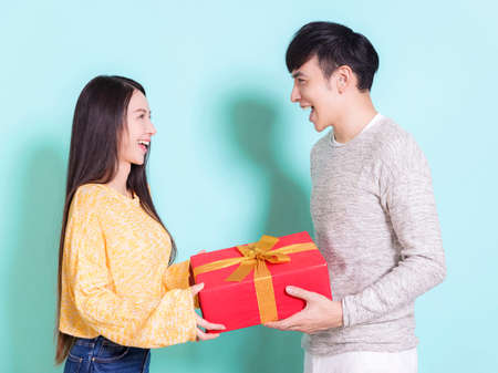 Happy young couple celebrating for chinese new year and holding gift box.Isolated on blue background.