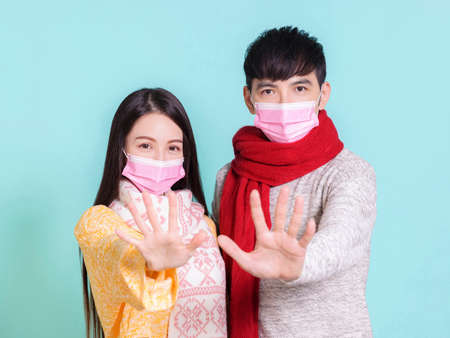 Young couple wearing winter clothes with medical mask showing stop gesture.Isolated on blue background. Фото со стока