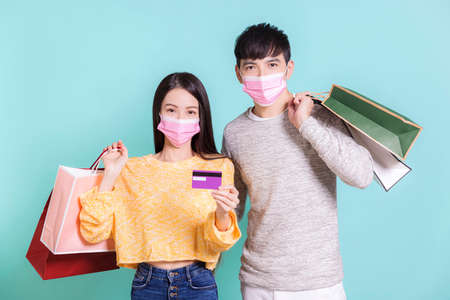 Young couple wearing winter clothes with medical mask  holding shopping bags and credit cards.Isolated on blue background.