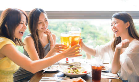 Happy young woman friends clinking glasses of beer in restaurant
