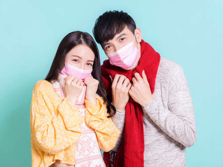 Young couple wearing winter clothes and  medical mask.Isolated on blue background.