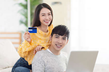 Young couple showing credit card and using laptop in the living room.