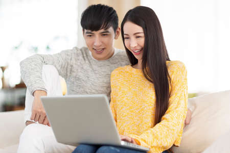 Young couple using laptop and watching video together in the living room. Фото со стока
