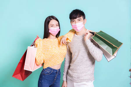 Young couple in medical mask and holding shopping bags