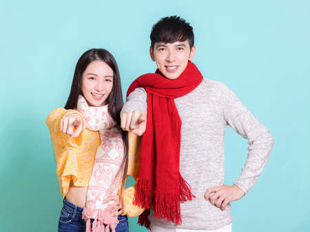 Young couple in winter clothes and hand pointing to camera