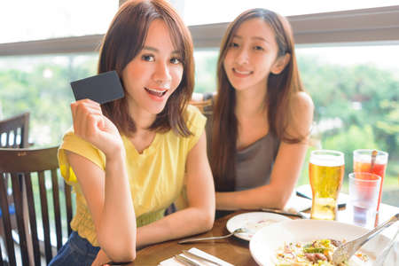 Beautiful  young women showing the credit card and paying in restaurant