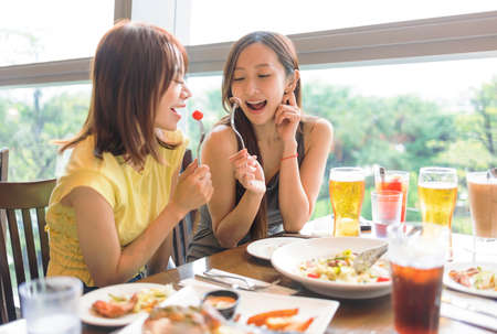 Happy  young woman enjoying food and drink in restaurant