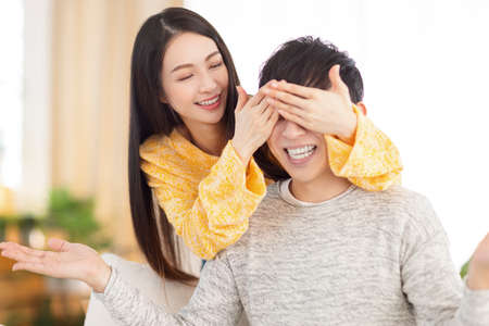 Smiling young woman covering her partner's eyes sitting on sofa. Young woman surprising man in the living room at home. Фото со стока