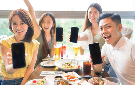Happy young group Showing mobile phone with blank screen in restaurant