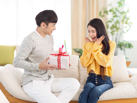 Young man giving a surprise gift to woman in the living room. Фото со стока