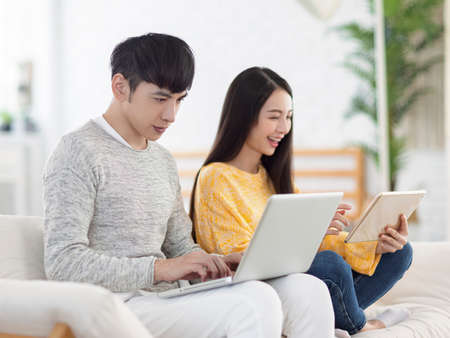 Young couple using laptop for office and watching movies on sofa at home