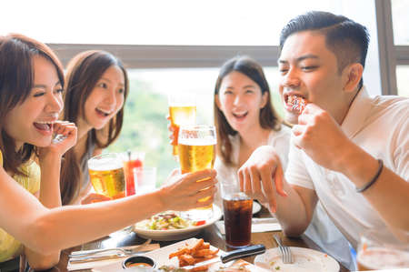Happy  friends enjoying food and drink in restaurant