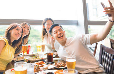 Happy young  group sitting in  restaurant and taking  selfie