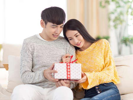 Young couple sharing gift in the living room.