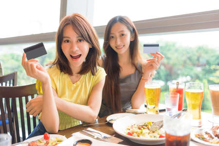 Beautiful young women showing the credit card in restaurant