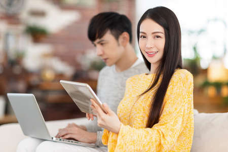 Young couple using laptop and tablet in the living room.