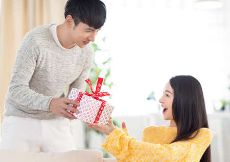 Young couple giving the gift box in living room
