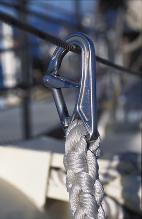cordage: Metal snap lock in use at sea attaching the end of a thick plaited woven rope or cordage to a strong metal cable or hawser allowing for quick attachment and release