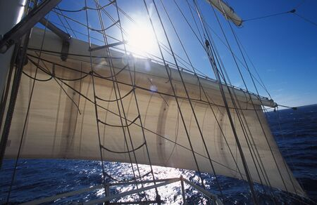 Bright sun flare shining over the top of a sail with rigging on a yacht at sea during a tropical summer vacation cruise Stock Photo