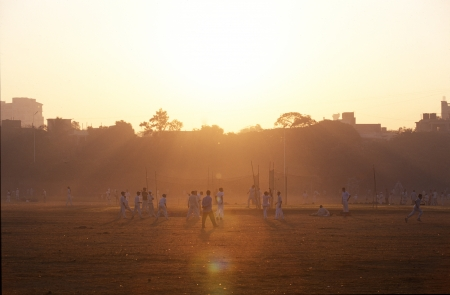Group of young Indians playing cricket in the glow of the early morning light with light mist or haze in the air in Mumbai