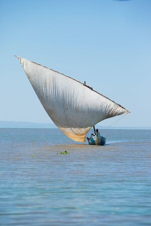 Arab or African dhow with a large lateen-rigged sail sailing through a calm ocean towards the camera Stock Photo - 19711004