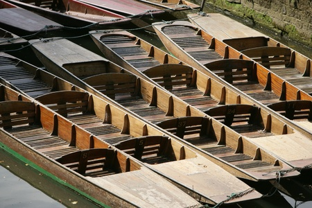 Row of wooden punts moored to the riverbank on the River Cherwell in Oxford, England for use by punters who wish to spend a relaxing day on the water