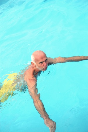 Senior man having a refreshing swim in a turquoise blue pool in a healthy lifestyle concept