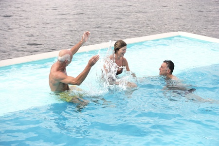 Three middle-aged friends playing in the pool splashing and romping as they enjoy the cool water Stock Photo - 19724201
