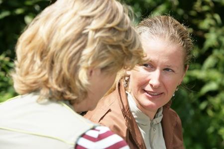 two people talking: Hermosa mujer sentada de mediana edad frente a la c�mara charlando con su amiga en un verde jard�n