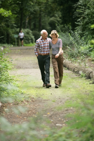Romantic elderly couple enjoying a walk strolling along a wooded footpath arm in arm photo