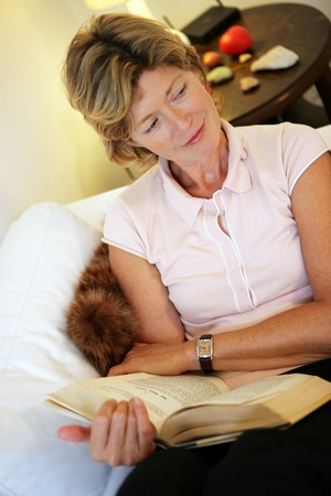 Beautiful older woman reading a book relaxing on a couch in her living room glancing sideways with a gentle smile Stock Photo