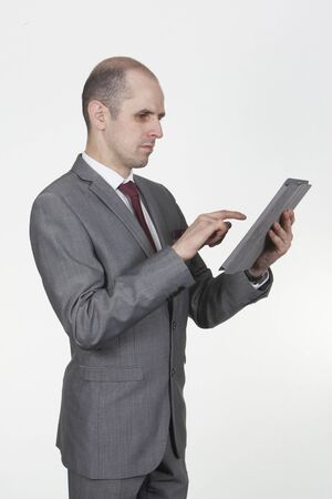Confident businessman standing sideways using his tablet computer reading the screen with his finger poised to add information via the touchscreen Stock Photo