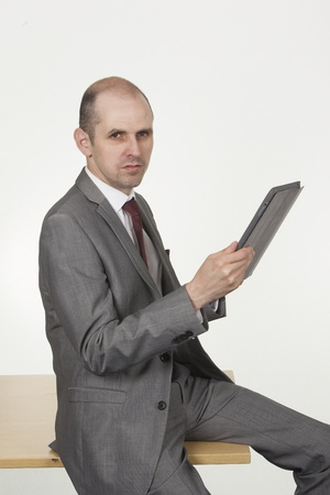 Middle aged businessman holding a talet-pc sitting on the edge of a wooden table looking at the camera