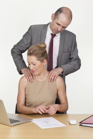 acoso laboral: El acoso sexual en el lugar de trabajo con un jefe var�n de pie detr�s de una empleada haciendo avances no solicitados y acariciando sus hombros Foto de archivo