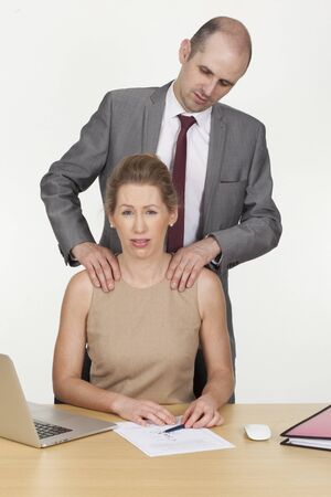 unsolicited: Sexual harassment in the workplace with a male boss standing behind a female employee making unsolicited advances and caressing her shoulders