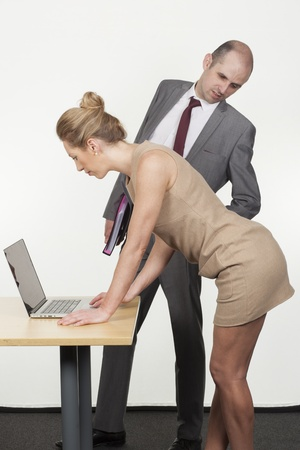 unsolicited: Sexual harassment by the boss in the workplace with a businessman bending over to ogle up under the skirt of a female colleague or secretary as she bends over a table to work on a laptop